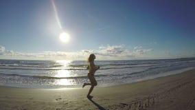 Jeune mise femelle sur des écouteurs et aller pour longtemps une course sur la plage banque de vidéos