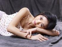 Jeune modèle asiatique sexy se trouvant sur le plancher photos stock