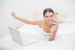 Jeune modèle d'une chevelure brun enthousiaste dans des pyjamas blancs faisant des emplettes en ligne avec son ordinateur portable Photos stock