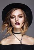 Jeune modèle dans le chapeau noir avec les yeux fumeux en bronze et les lèvres rouges Images stock