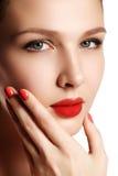 Jeune modèle de belle femme avec les lèvres rouges et la manucure rouge beau Photographie stock
