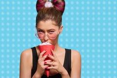 Jeune modèle de fantaisie mangeant la crème du klaxon rouge image stock