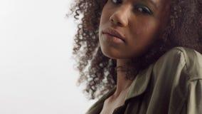 Jeune modèle de métis dans le studio sur le blanc avec les cheveux bouclés, maquillage vert clair d'oeil clips vidéos