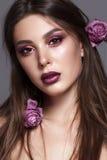 Jeune modèle de Taned avec le maquillage professionnel et roses défraîchies dans les cheveux Images libres de droits