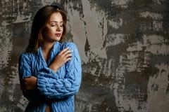 Jeune modèle tendre portant le manteau tricoté, posant avec des ombres L'espace vide photo stock