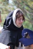 Jeune moine Watching un affichage aux ruisseaux annuels Faire médiéval Photographie stock libre de droits