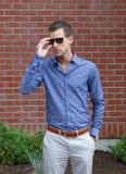 Jeune monsieur mettant sur ses lunettes de soleil photographie stock libre de droits