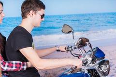 Jeune moto d'équitation de couples à la plage Photo libre de droits