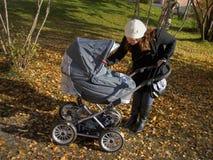 Jeune mère avec la voiture d'enfant Photo stock