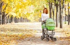 Jeune mère heureuse avec la chéri dans la poussette Image stock