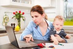 Jeune mère travaillant avec son bébé Photo libre de droits