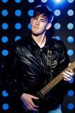 Jeune musicien attirant de roche jouant la guitare électrique et le chant Vedette du rock sur le fond des projecteurs Photo stock