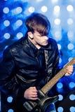 Jeune musicien attirant de roche jouant la guitare électrique et le chant Vedette du rock sur le fond des projecteurs Photos libres de droits