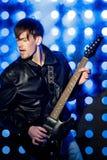 Jeune musicien attirant de roche jouant la guitare électrique et le chant Vedette du rock sur le fond des projecteurs Photographie stock libre de droits