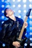 Jeune musicien attirant de roche jouant la guitare électrique et le chant Vedette du rock sur le fond des projecteurs Image stock