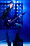 Jeune musicien attirant de roche jouant la guitare électrique et le chant Vedette du rock sur le fond des projecteurs Image libre de droits
