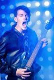Jeune musicien attirant de roche jouant la guitare électrique et le chant Vedette du rock sur le fond des projecteurs Photographie stock