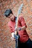 Jeune musicien beau jouant la guitare photographie stock libre de droits