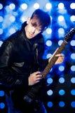 Jeune musicien de roche jouant la guitare électrique et le chant Vedette du rock sur le fond des projecteurs Photographie stock