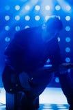 Jeune musicien de roche jouant la guitare électrique et le chant Vedette du rock sur le fond des projecteurs Photos stock