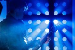 Jeune musicien de roche jouant la guitare électrique et le chant Vedette du rock sur le fond des projecteurs Image stock