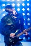 Jeune musicien de roche jouant la guitare électrique et le chant Vedette du rock sur le fond des projecteurs Photo libre de droits