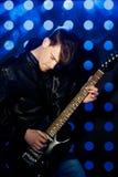 Jeune musicien de roche jouant la guitare électrique et le chant Vedette du rock sur le fond des projecteurs Images stock