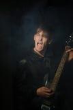 Jeune musicien de roche jouant la guitare électrique et le chant Vedette du rock sur le fond des projecteurs Image libre de droits