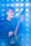 Jeune musicien de roche jouant la guitare électrique et le chant Vedette du rock sur le fond des projecteurs Photos libres de droits