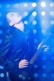 Jeune musicien de roche jouant la guitare électrique et le chant Vedette du rock sur le fond des projecteurs Photo stock