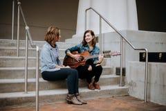 Jeune musicien féminin mignon Friends Modeling Outside sur des pas concrets photos libres de droits