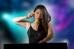 Jeune musique de remélange de belle et attirante de Chinois femme asiatique du DJ aux écouteurs de port de boîte de nuit d'iso photos stock