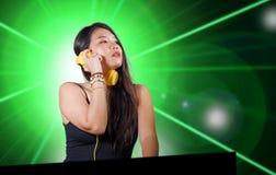 Jeune musique de remélange de belle et attirante femme coréenne asiatique du DJ aux écouteurs de port de boîte de nuit d'isol images stock