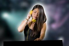 Jeune musique de remélange de belle et attirante femme japonaise asiatique du DJ aux écouteurs de port de boîte de nuit en par image libre de droits