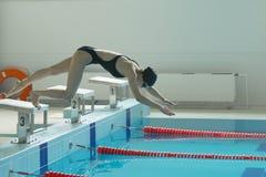 Jeune nageur féminin, ce sauter et plonger dans la piscine de sport d'intérieur photographie stock