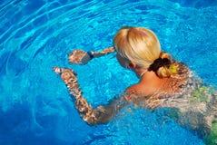 Jeune natation adulte de fille dans le regroupement Photographie stock libre de droits