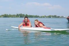 Jeune natation de couples avec le panneau de palette dans le lac Images stock