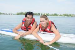 Jeune natation de couples avec le panneau de palette dans le lac Photo libre de droits