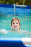 Jeune natation de garçon dans un regroupement extérieur Photographie stock
