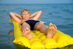 Jeune natation de garçon sur le matelas en mer photographie stock libre de droits