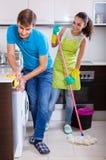 Jeune nettoyage de couples à la cuisine Images libres de droits