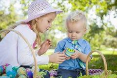 Jeune oeufs mignons d'Enjoying Their Easter de frère et de soeur dehors Photographie stock