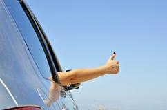 Jeune ok de geste de main avec l'hublot de véhicule. Image libre de droits