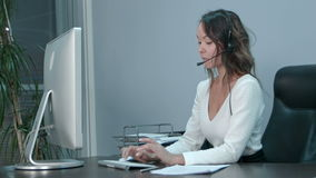 Friendly young asian female operator working on laptop with headset at modern office Stock Footage