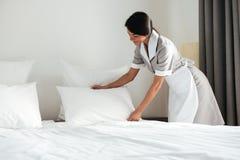 Jeune oreiller d'établissement de domestique d'hôtel sur le lit photos stock