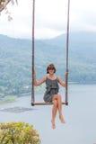 Jeune oscillation aldy sexy au-dessus du précipice sur l'île tropicale magique de Bali, Indonésie Photos libres de droits