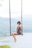 Jeune oscillation aldy sexy au-dessus du précipice sur l'île tropicale magique de Bali, Indonésie Images libres de droits