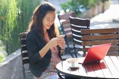 Jeune oudoor de travail de femme d'affaires, dans un café image stock