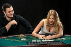 Jeune ouple de  de Ñ jouant le tisonnier, femme prenant des jetons de poker après gain Photographie stock