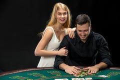 Jeune ouple de  de Ñ jouant le tisonnier Homme prenant des jetons de poker après gain Photo stock